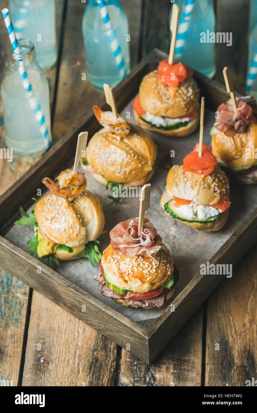 Home party food concept. Homemade burgers in wooden tray and lemonade in bottles with straws on rustic wooden table - Stock Image