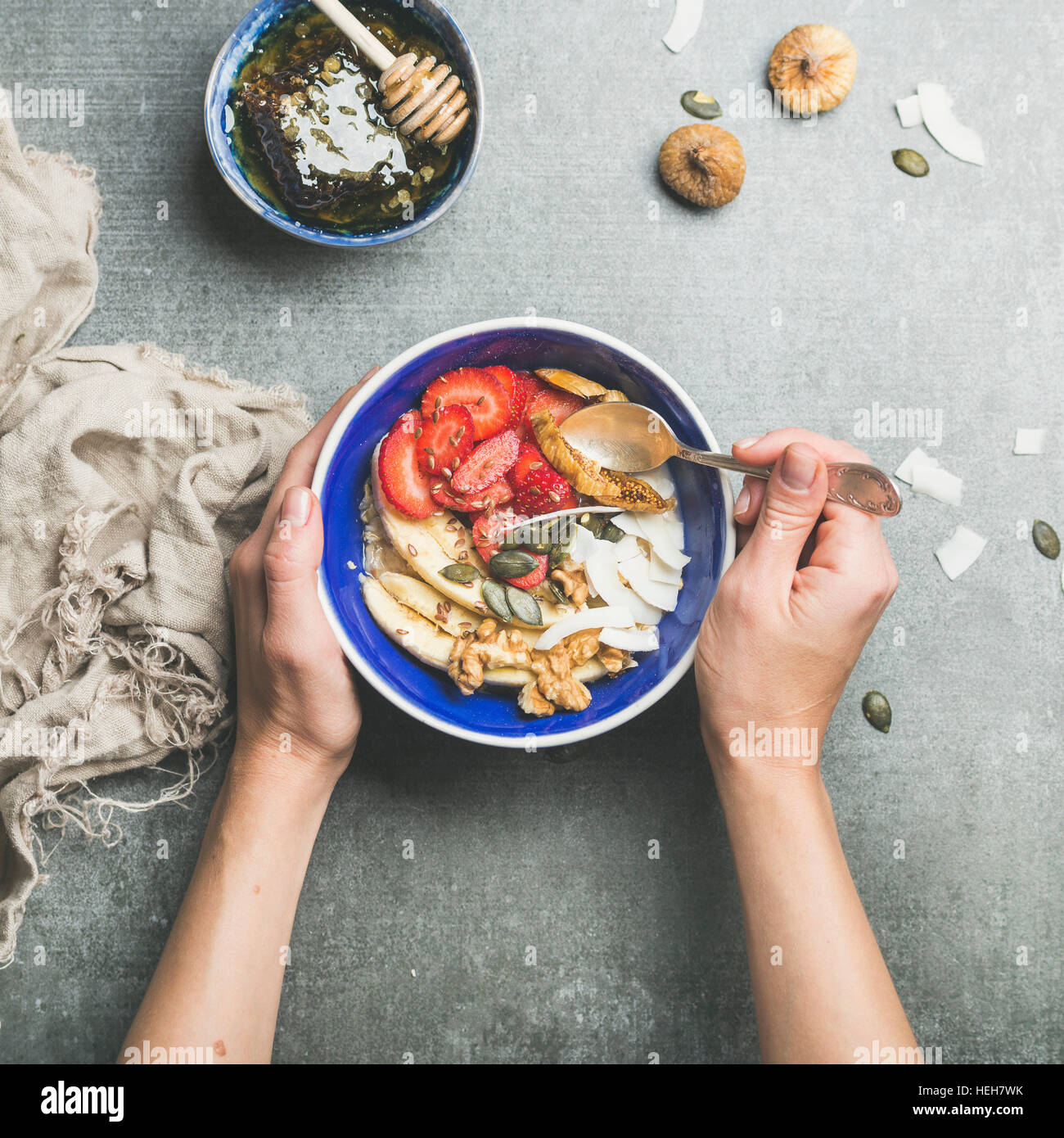 Yogurt, granola, seeds, fresh and dry fruit and honey in blue ceramic bowl in woman' s hands over grey concrete - Stock Image