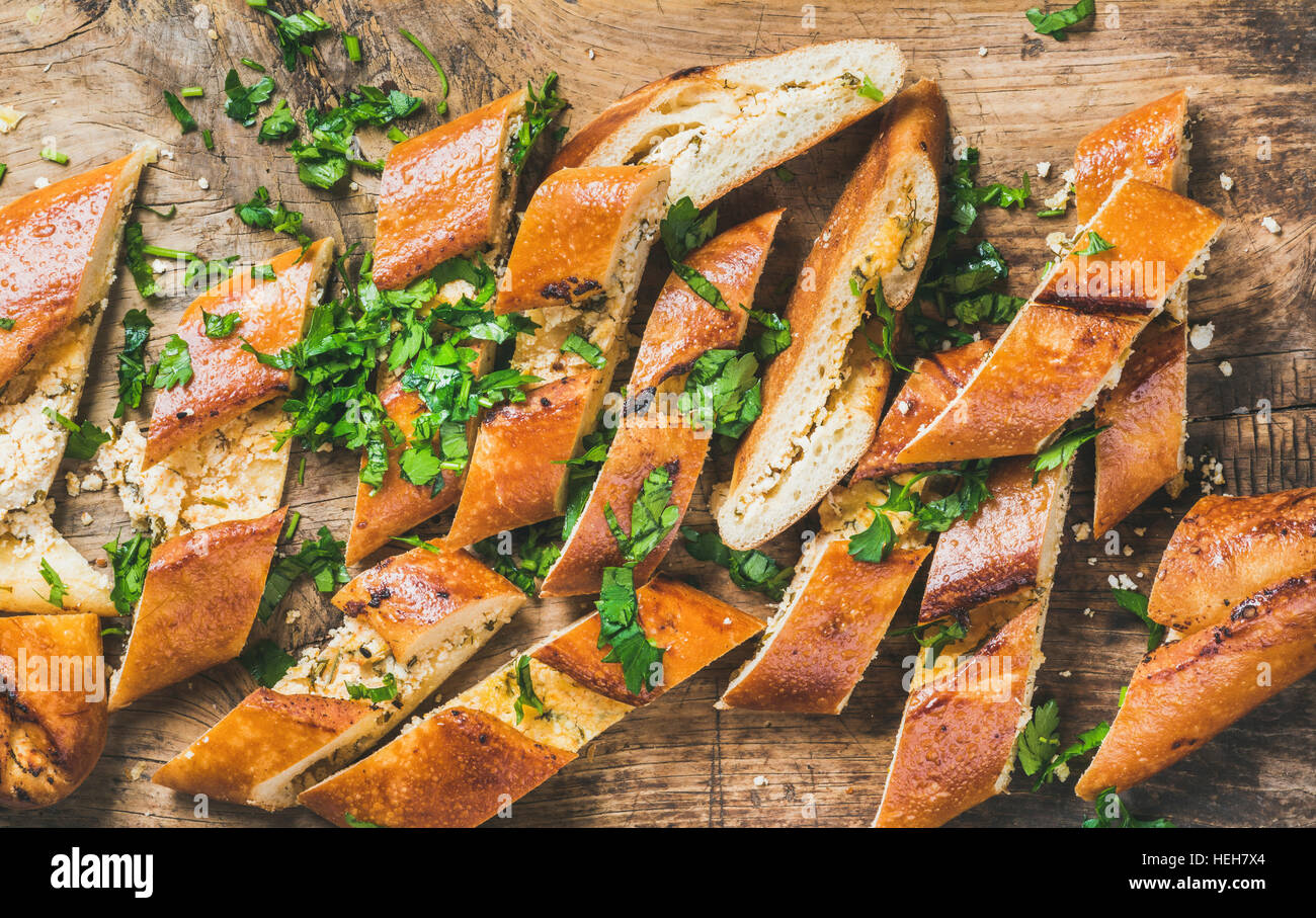 Close-up of Turkish oriental pizza pide with cheese and spinach chopped in slices on rustic wooden background, top - Stock Image