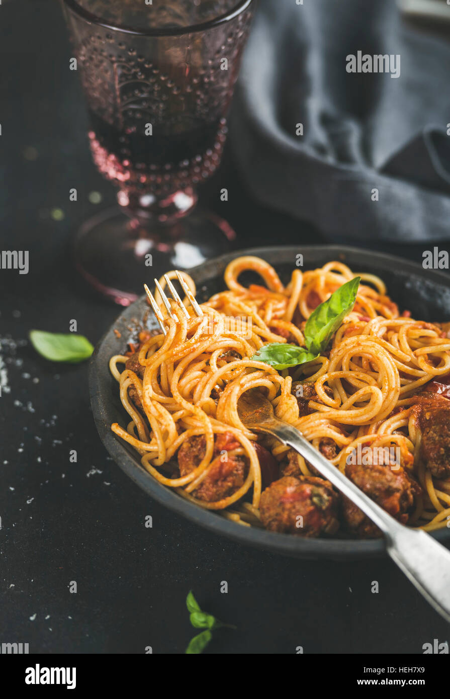 Italian pasta dinner. Spaghetti with meatballas, fresh basil leaves in dark plate and red wine in vintage glass - Stock Image