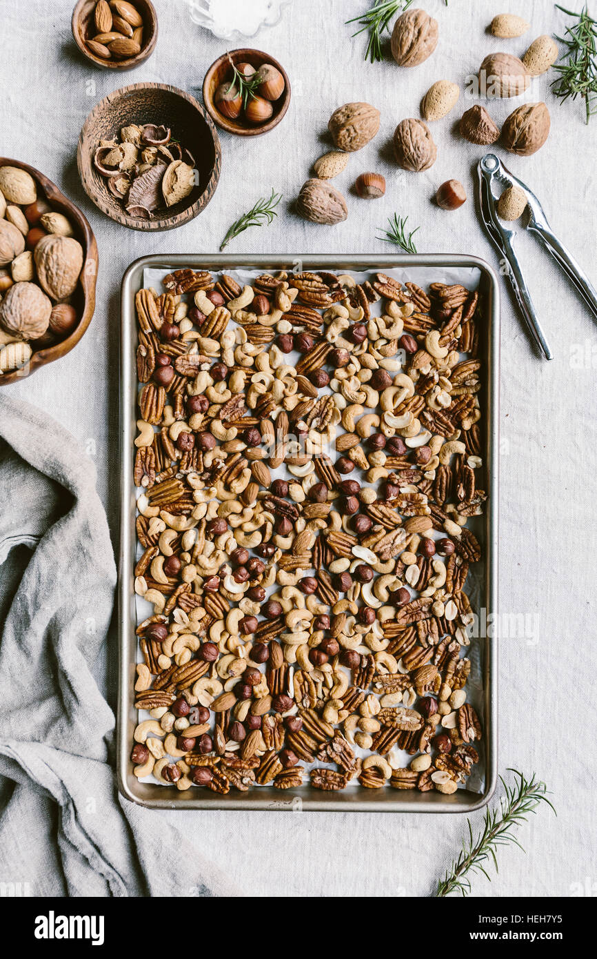 A few cups of mixed nuts are placed on a rimmed baking sheet to be toasted in the oven. - Stock Image