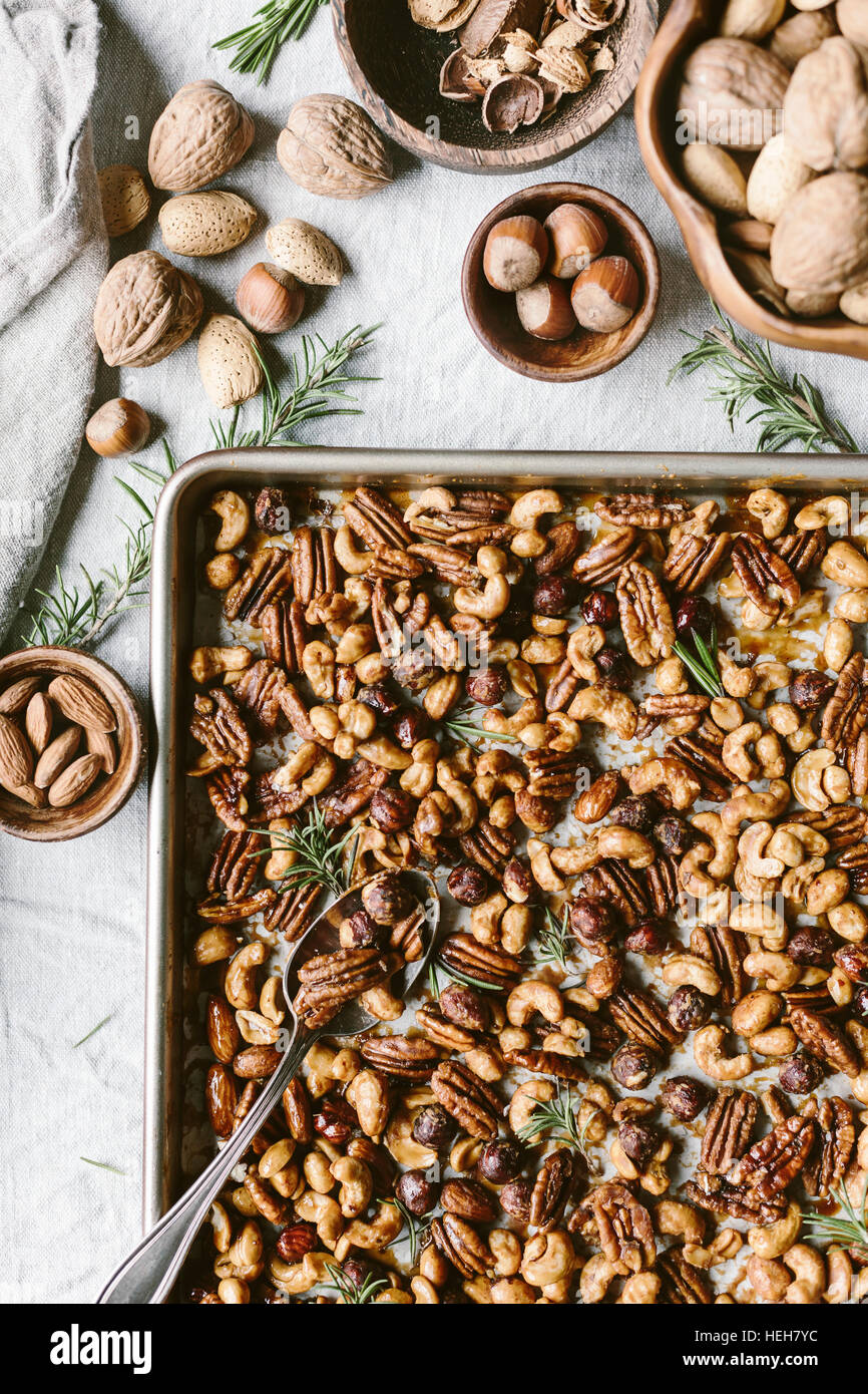 Spicy candied nuts are flavored with fresh rosemary leaves and photographed from the top view. - Stock Image