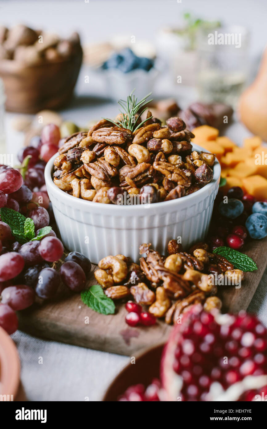 A bowl of spicy candied pecans are photographed from the front view as a part of a cheese and fruit board. - Stock Image