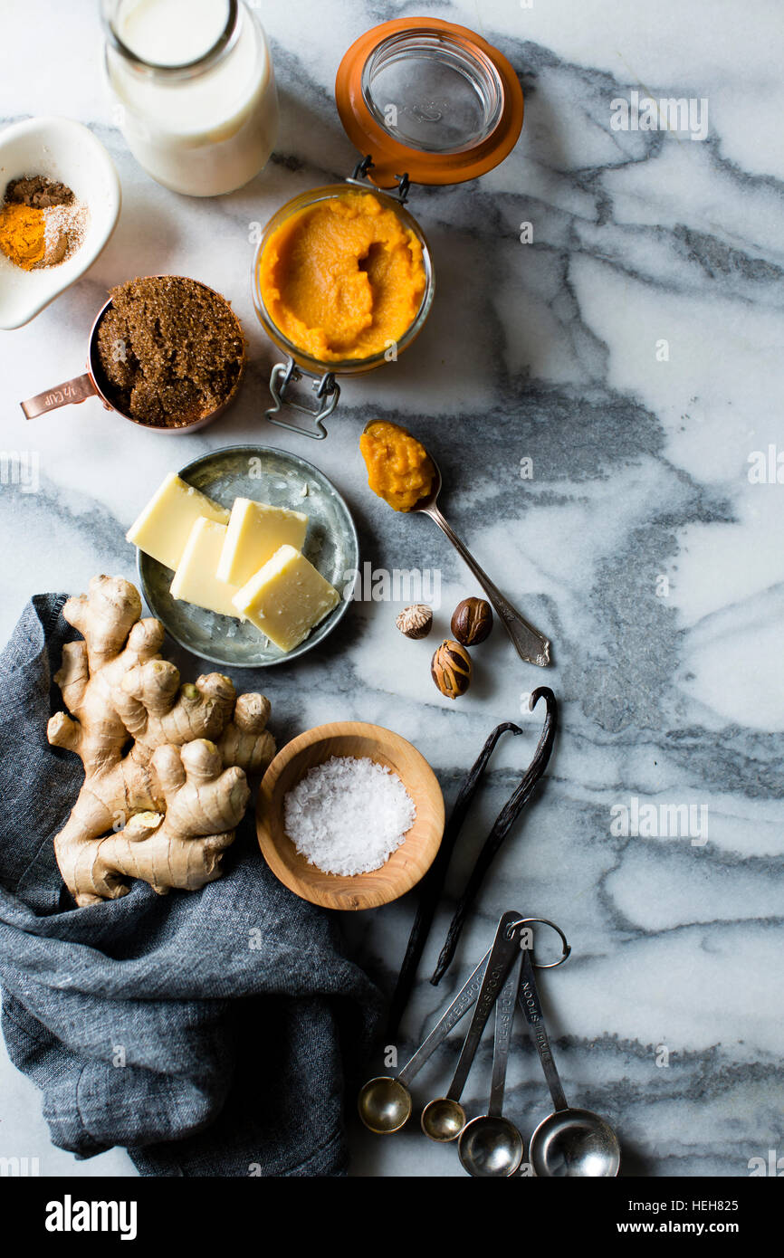 Cookery ingredients on marble work surface. Butter, ginger, milk, spices. - Stock Image