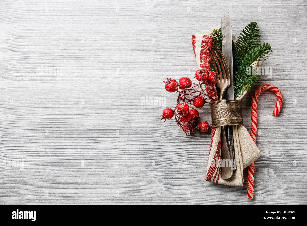 Table fork and knife set with napkin, christmas fir branch, red berries and napkin ring on gray wooden background - Stock Image
