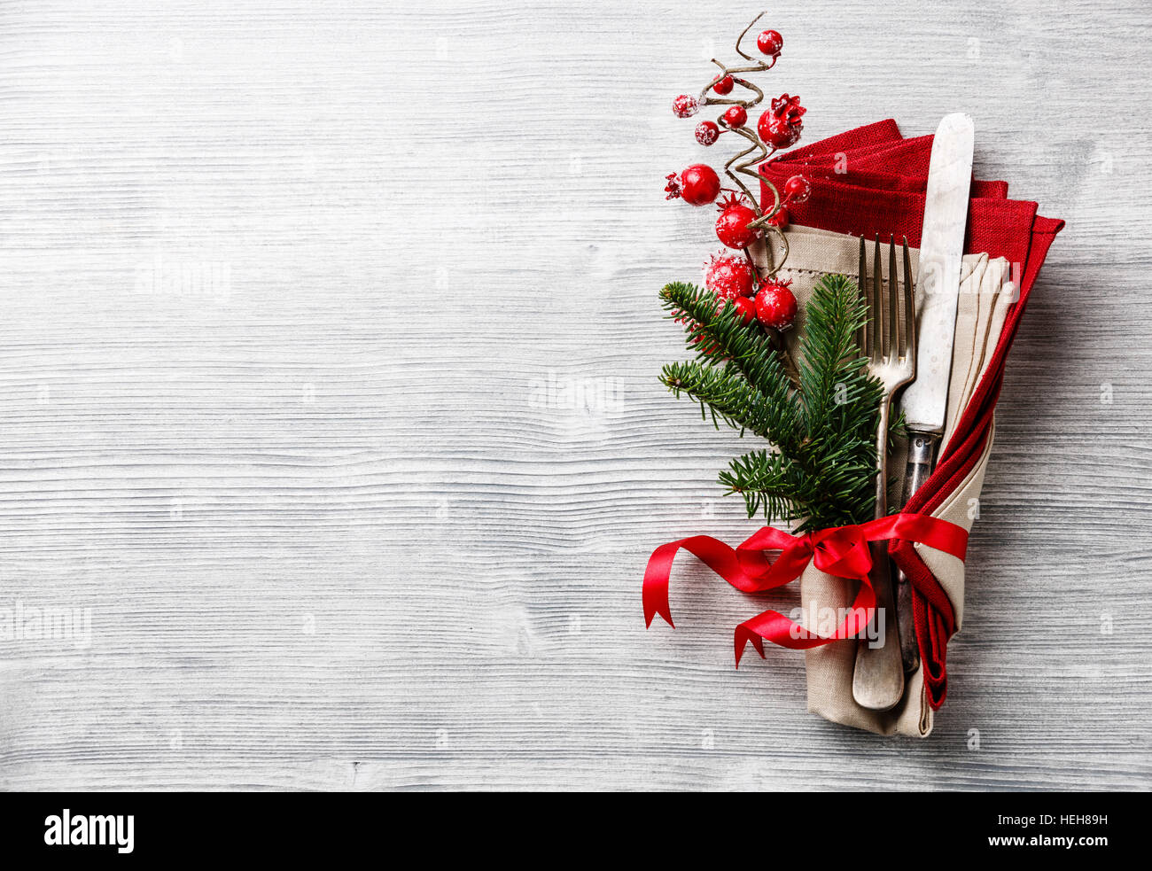 Table fork and knife set with napkin, christmas fir branch, red berries and ribbon on gray wooden background copy - Stock Image