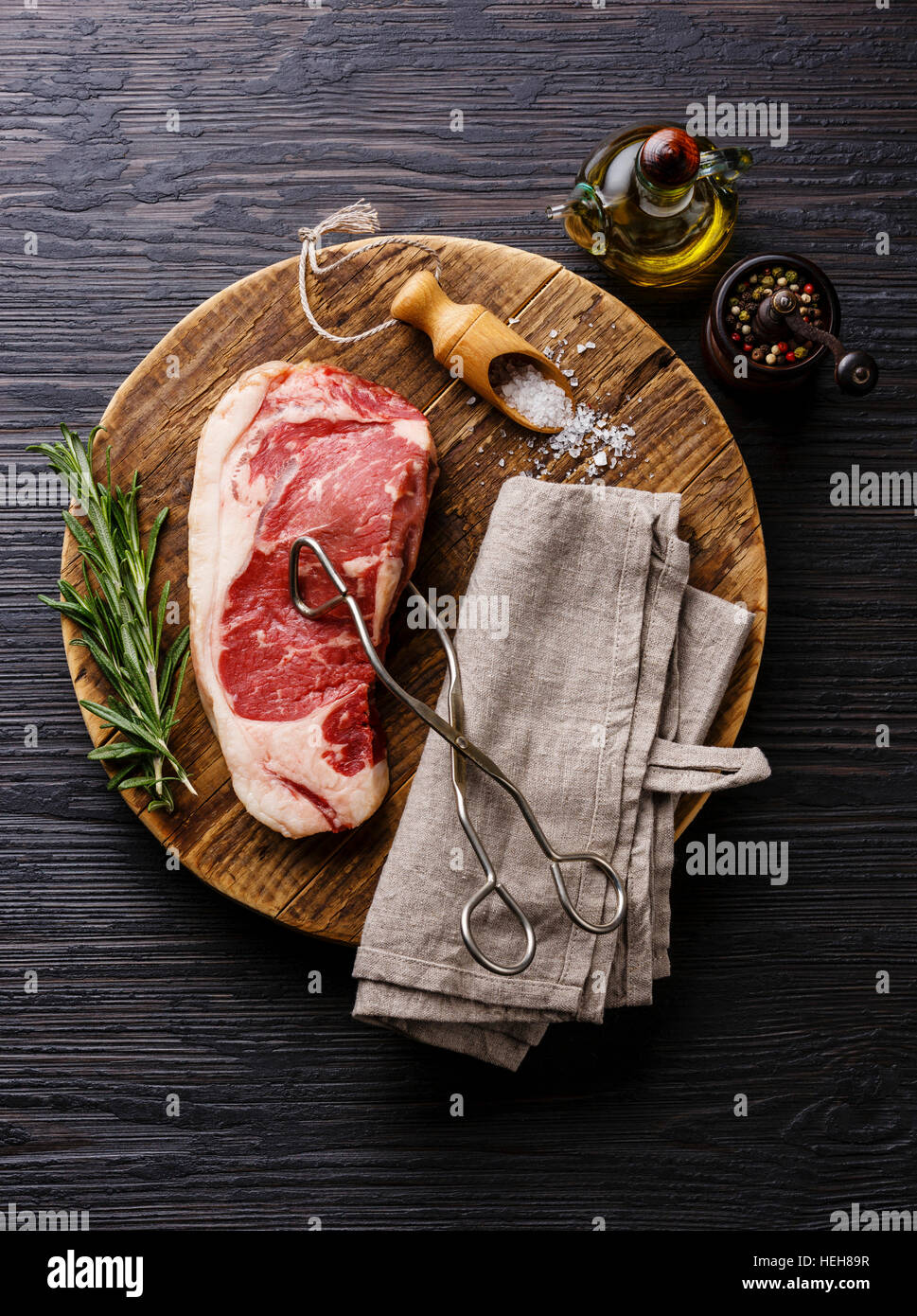 Raw fresh meat steak Striploin with salt and pepper and scissor tongs on cutting board on Black Burned wooden background - Stock Image