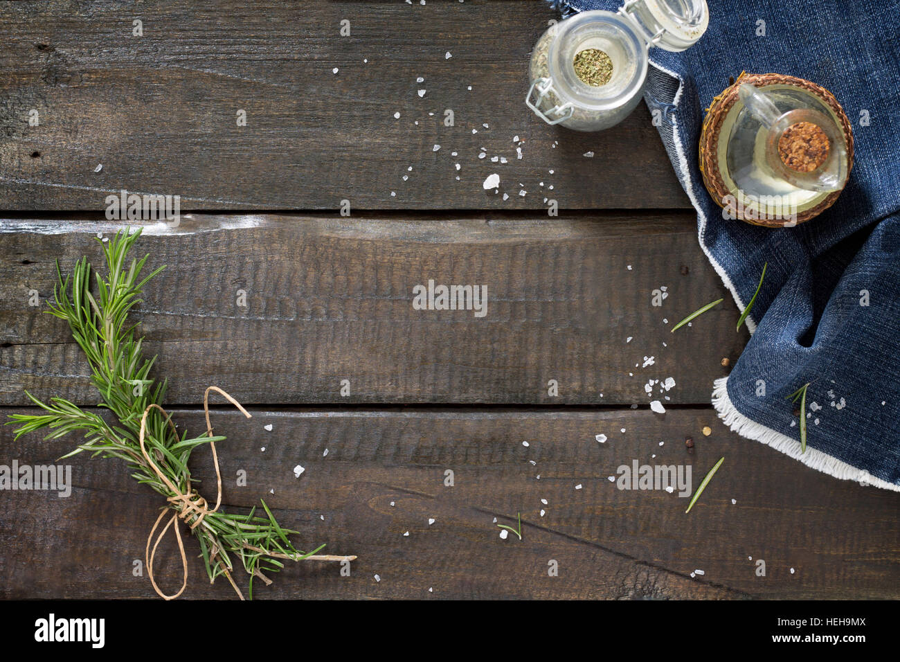 Sprigs of rosemary tied with string, oil and spices on a wooden table. Copy space. - Stock Image
