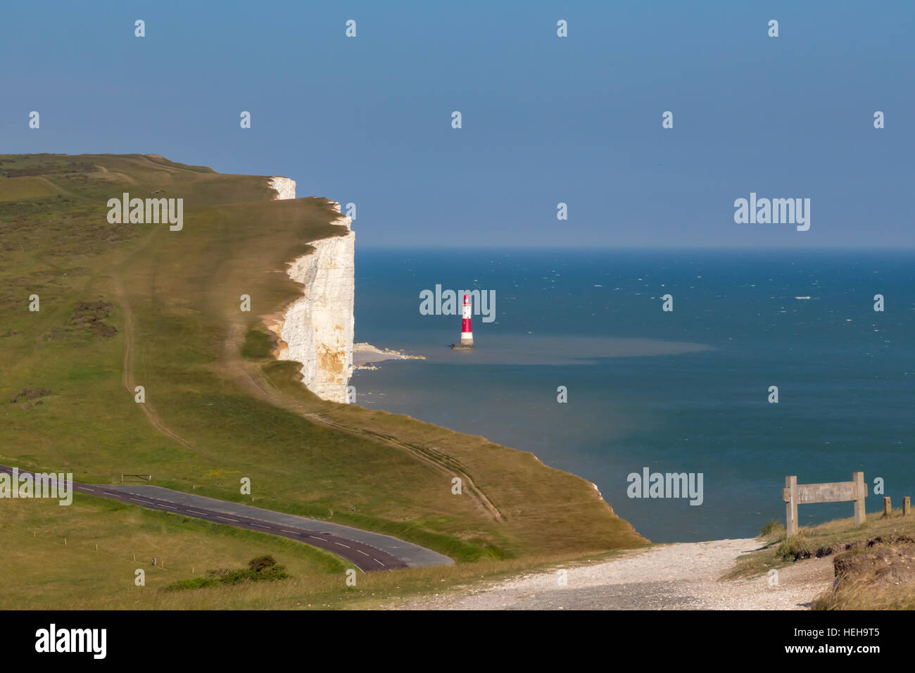 Looking at Beachy Heady with the lighthouse on a bright summer's day.  Shows a road, and a hiking track. - Stock Image