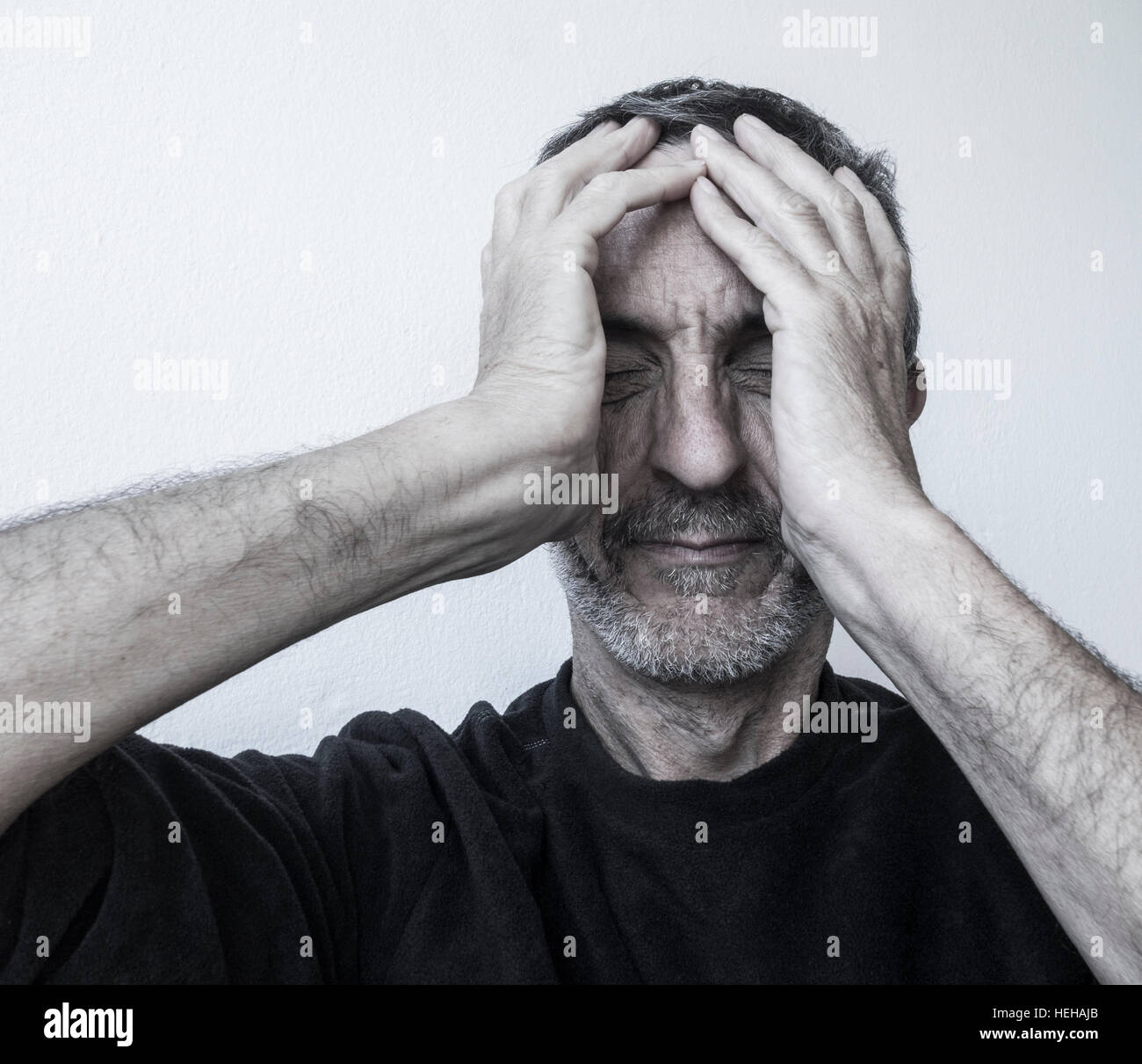 Mature man in his fifties holding his head: Depression, mental health, anxiety...concept image - Stock Image
