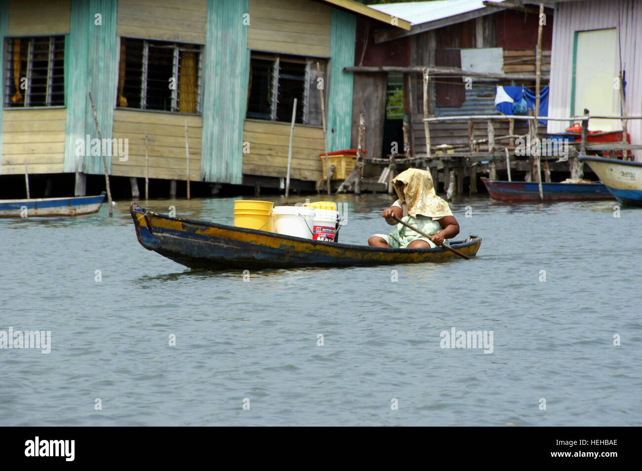 Woman carries a cargo boat. Fishing village on the water.  Mengkabong river, Kota Kinabalu, Sabah, Borneo, Malaysia. - Stock Image