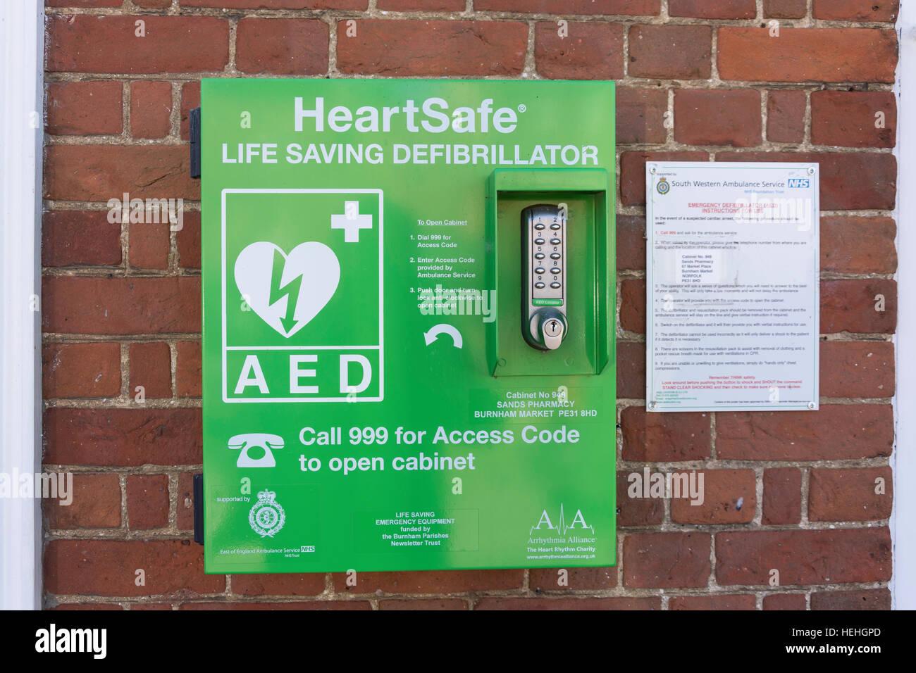 HeartSafe Life Saving Defribrillator on exterior wall, The Green, Market Place, Burnham Market, Norfolk, England, - Stock Image