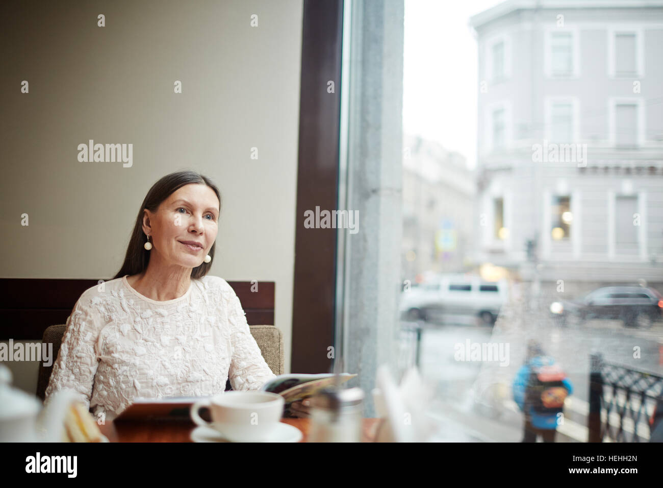 Pretty senior woman relaxing in cafe at lesiure - Stock Image