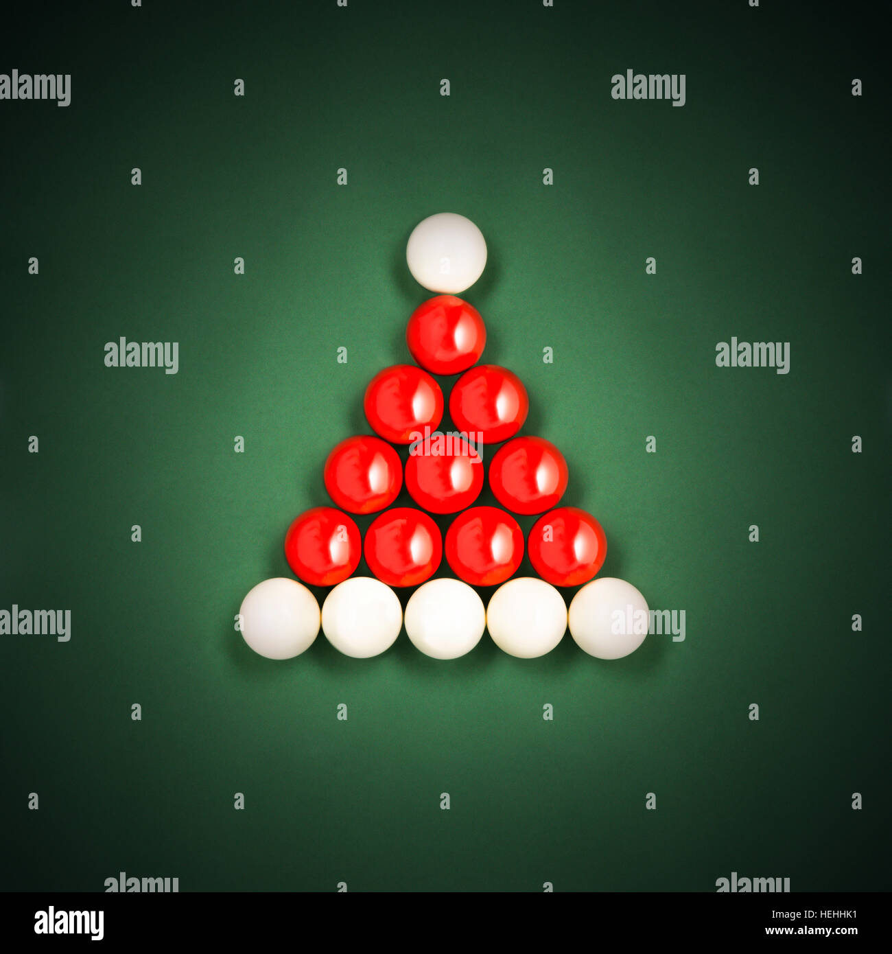 Snooker Ball Santa Hat Christmas cards made of red snooker balls and white cue balls on a green background - Stock Image