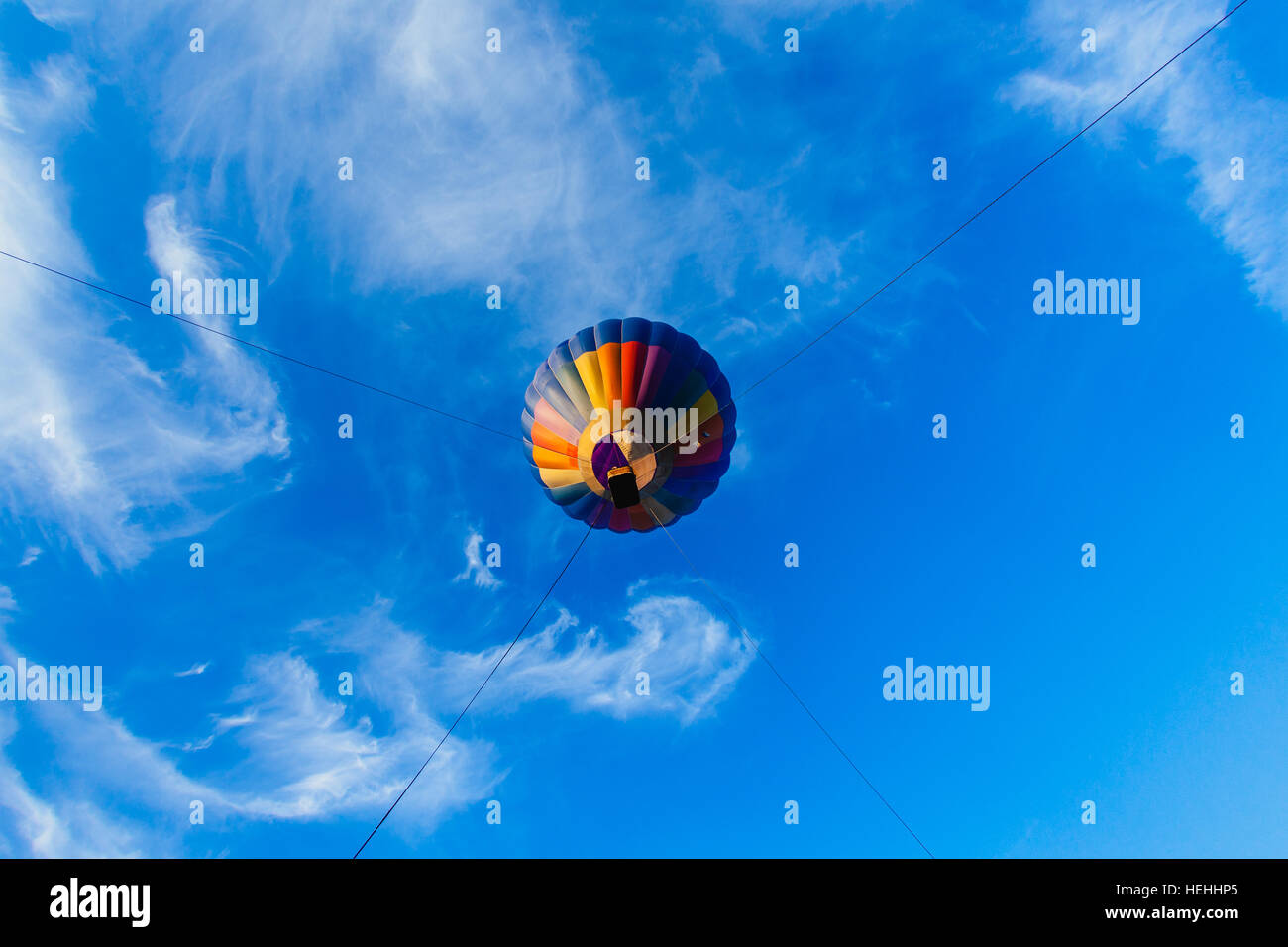 Colorful hot air balloon in blue sky at sunset - Stock Image
