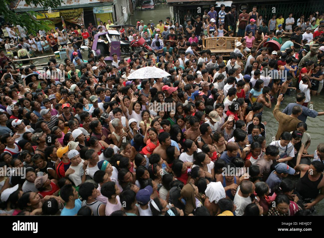 Local Filipino citizens wait in line to receive disaster relief supplies donated by the ABS-CBN Television Network - Stock Image