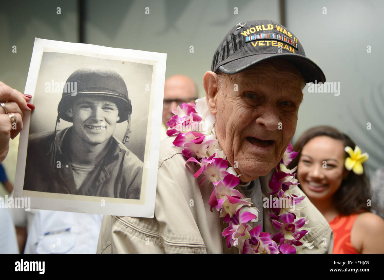 A U.S. Navy World War II veteran holds up a photo of himself after arriving at the Honolulu International Airport - Stock Image