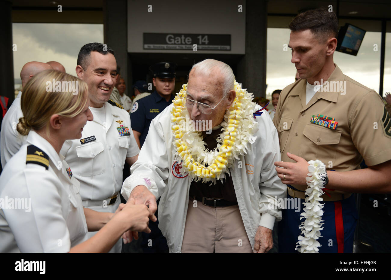 A World War II Pearl Harbor U.S. veteran is greeted by U.S. soldiers with floral leis after arriving at the Honolulu - Stock Image