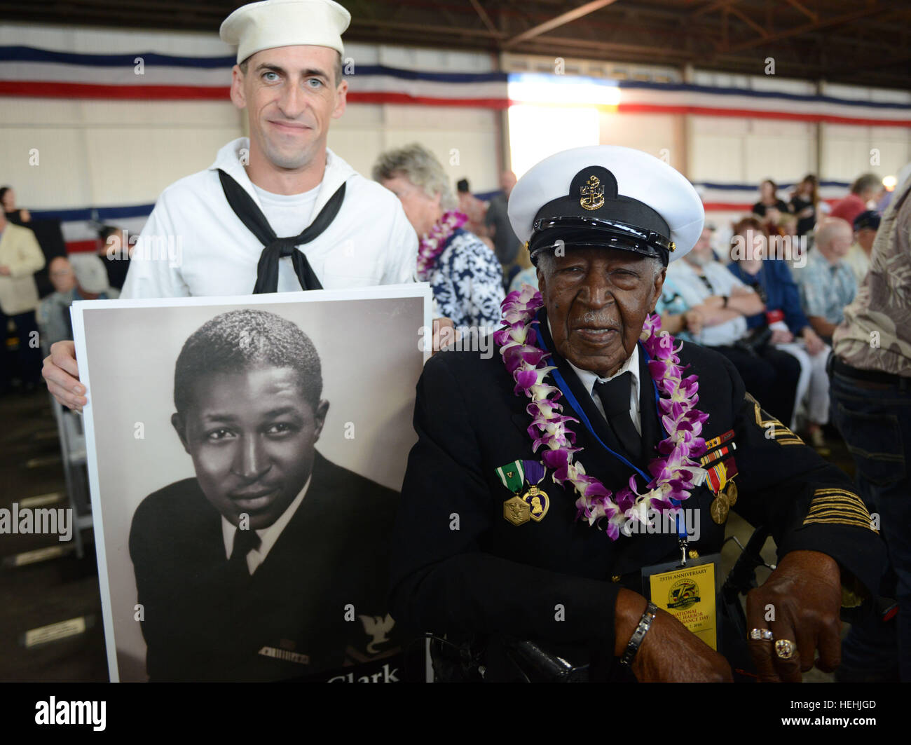 U.S. World War II veteran and Pearl Harbor survivor Carl Clark poses next to a younger portrait of himself during - Stock Image