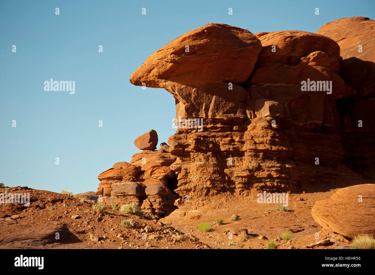 Rock formation in Canyon-land National Park Utah.  Red rock formation created by wind erosion with small bushes - Stock Image
