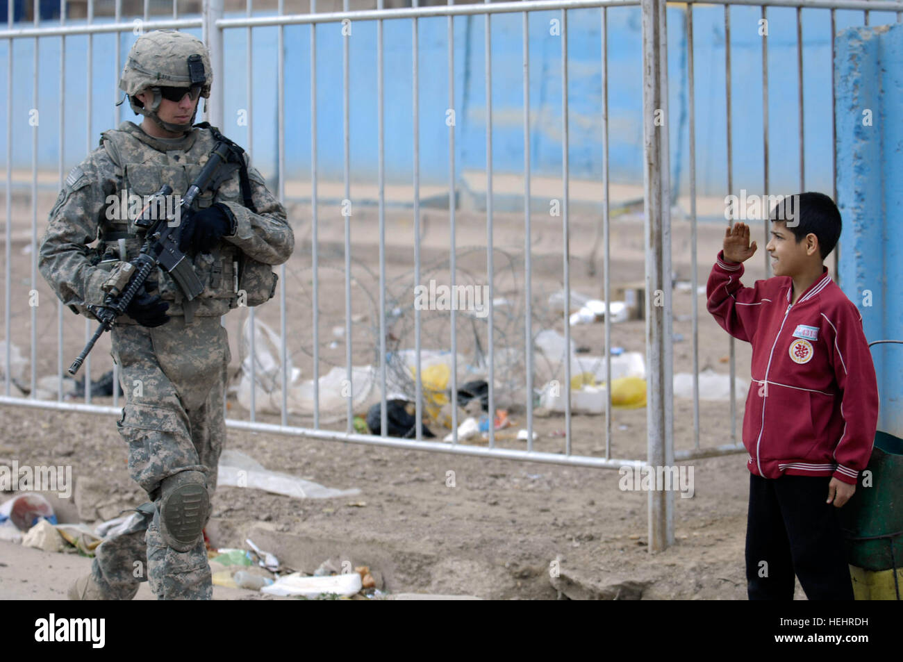 A young Iraqi boy stands and salutes Spc. Todd Bair of the1st Battalion, 505th Parachute Infantry Regiment, 3rd - Stock Image
