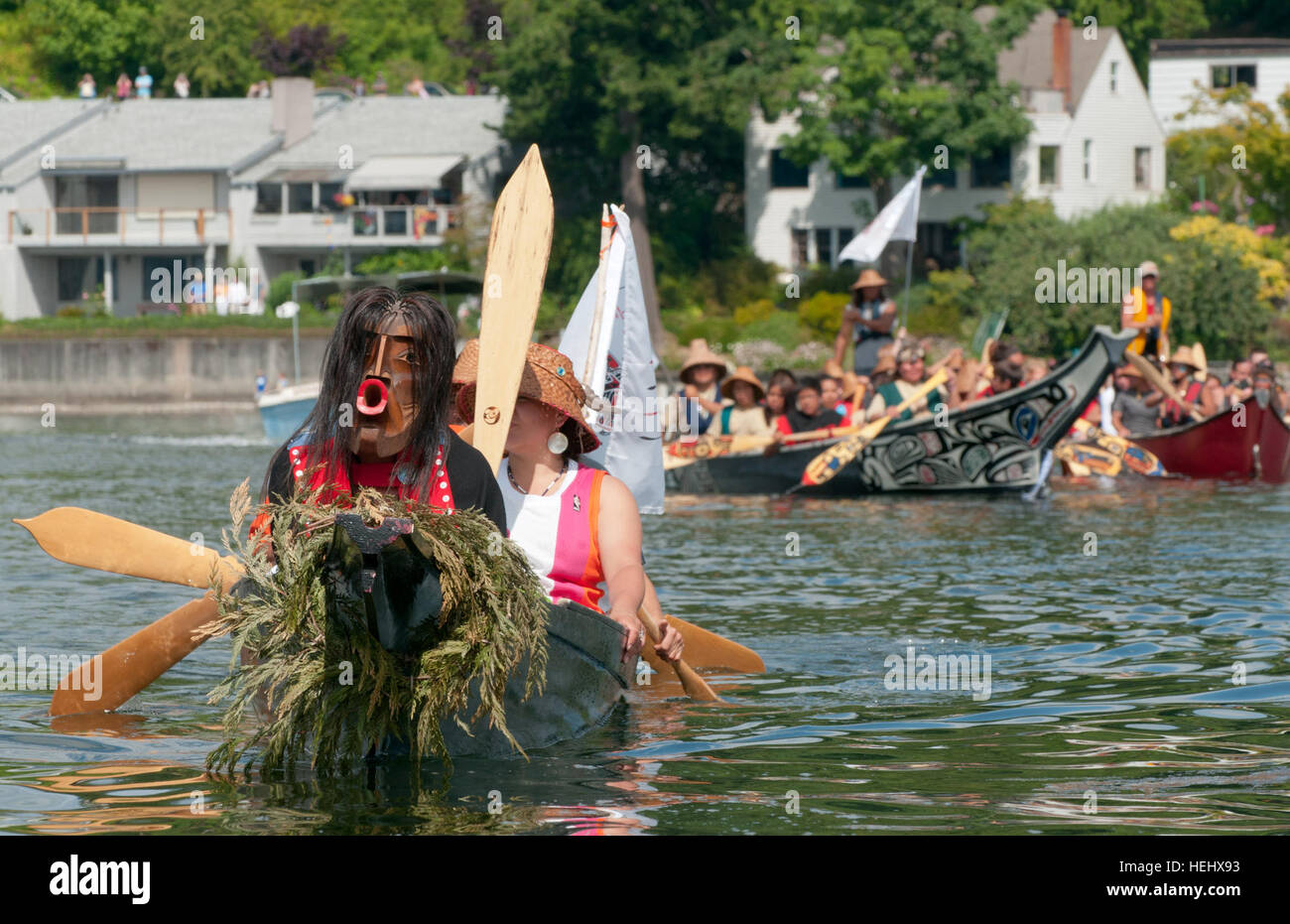 In the final step of their canoe journey, Native Americans row toward the ramp to have their watercraft pulled onto - Stock Image