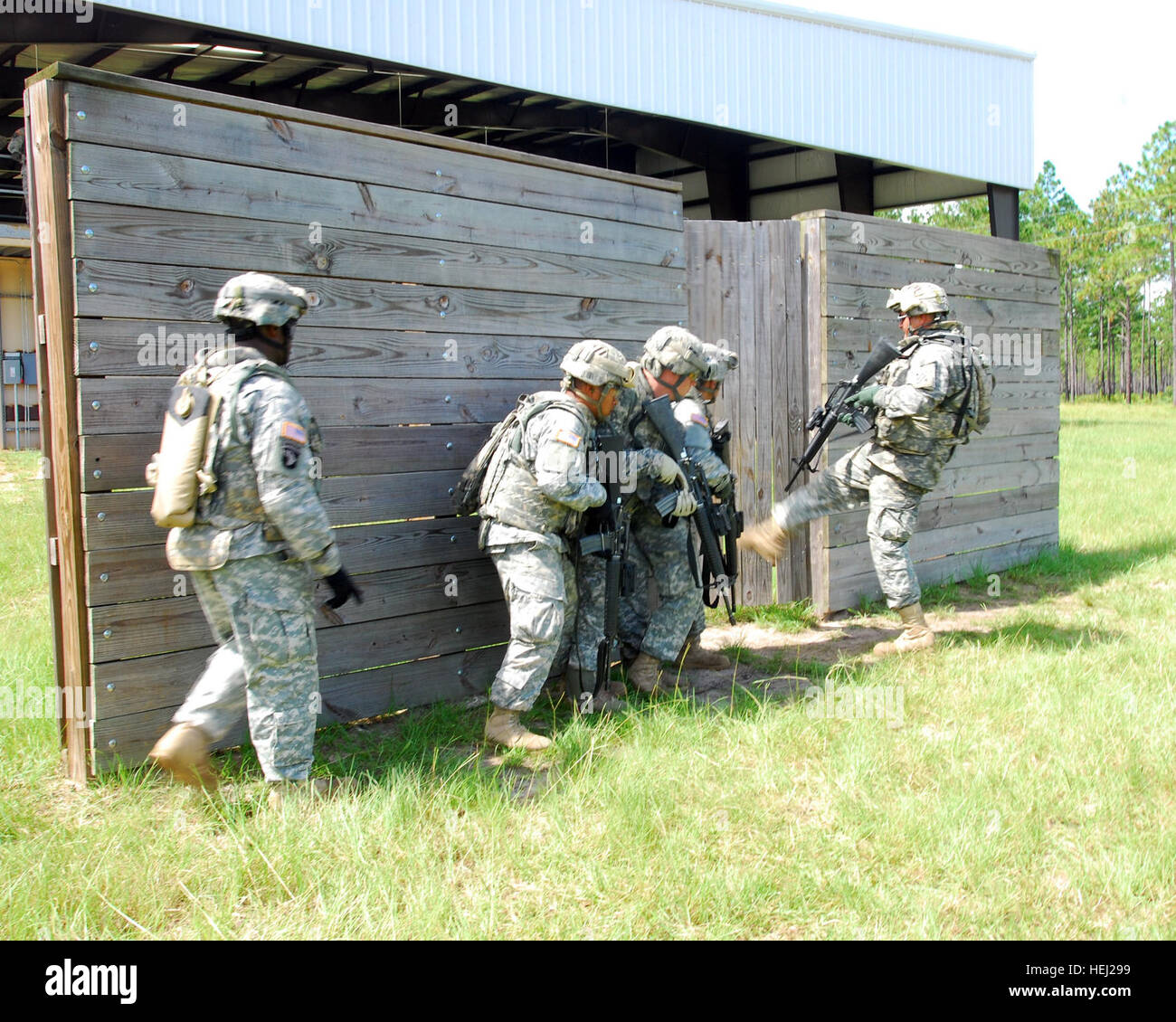 Soldiers from E Co., 4-3 Avn., begin their urban terrain (mout) live-fire exercie Aug. 26, by kicking a door at - Stock Image