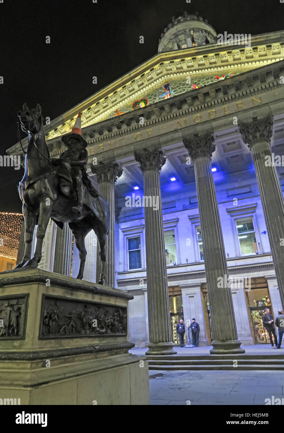 Glasgow buildings of the Merchant City,Scotland,UK at night - GOMA and traffic cone on head of Duke Of Wellington Stock Photo