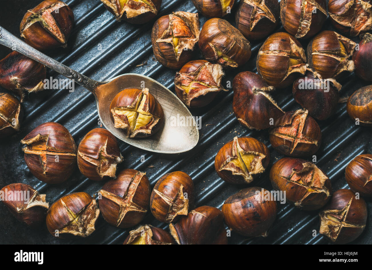 Close-up of roasted chestnuts and metal vintage spoon in pan - Stock Image