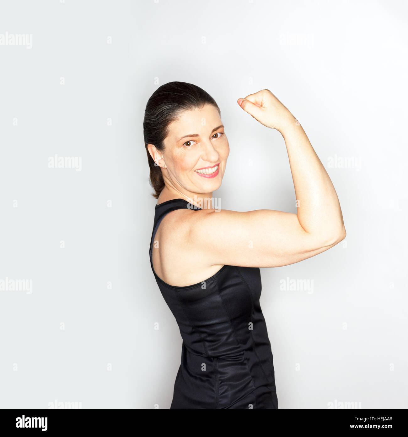 Self-confident adult woman in black muscleshirt showing her bisceps muscles, light background, responsive design, - Stock Image