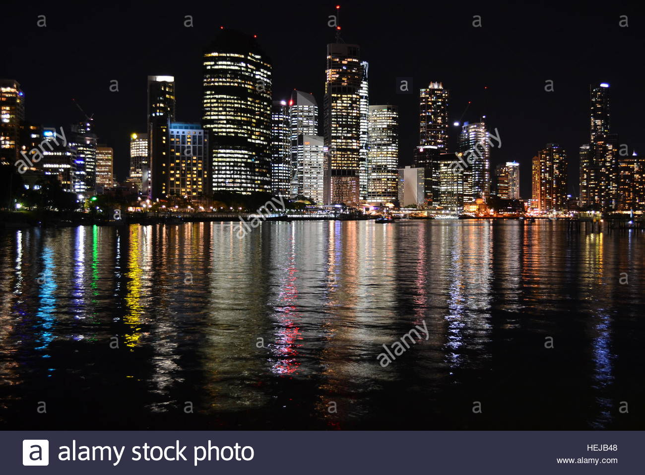 Brisbane Skyline at night, city lights creating colorful reflections in the water - Stock Image