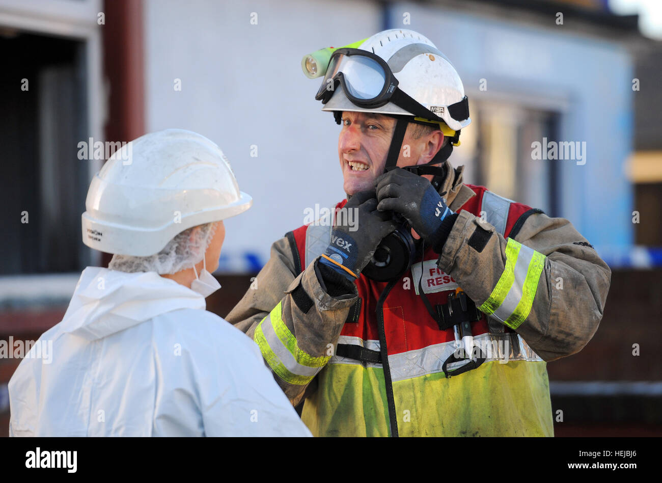 A fire investigation officer (right) talks to a police forensic officer outside a house in Braintree, Essex, after - Stock Image