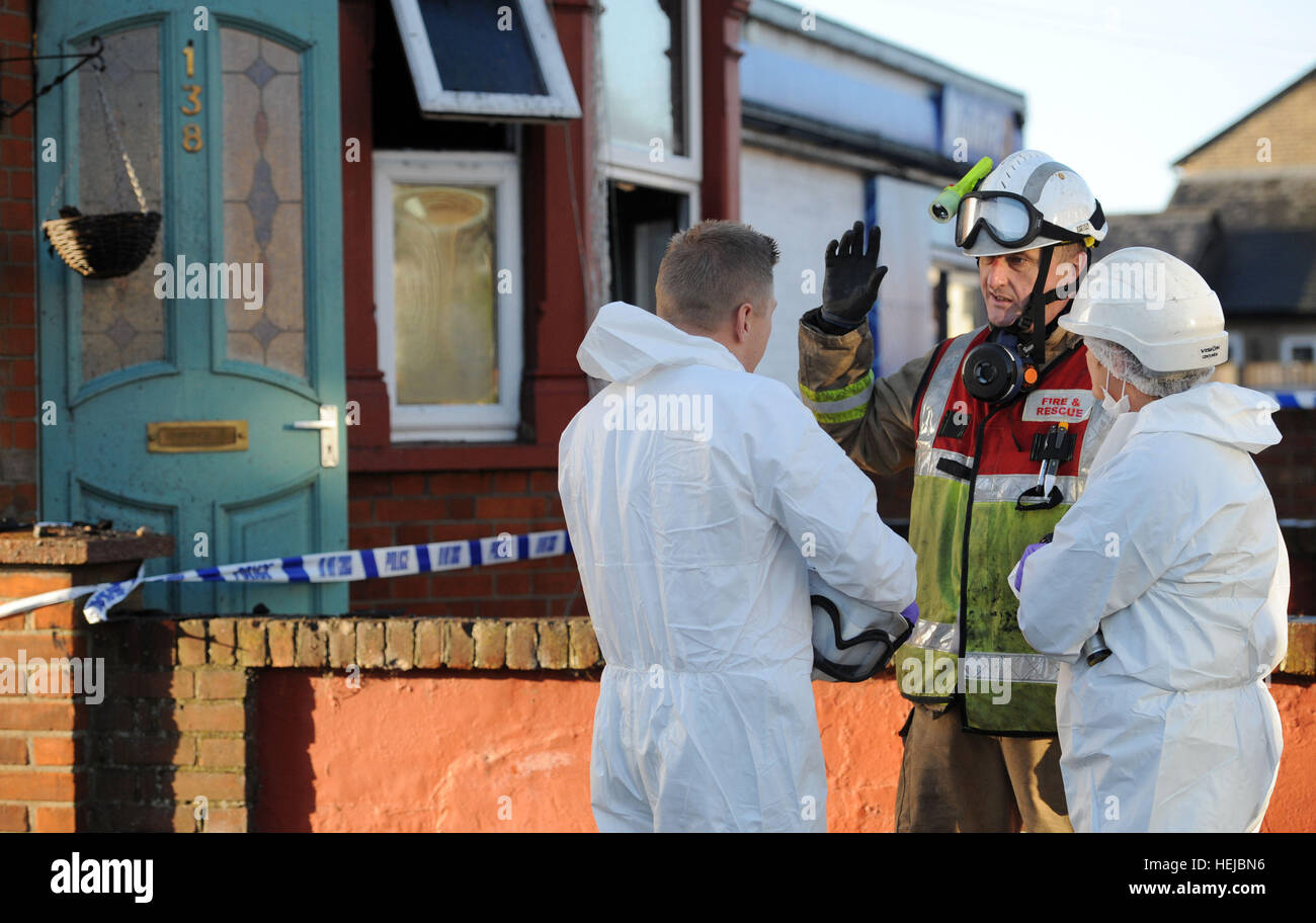 A fire investigation officer (centre) talks to police forensic officers outside a house in Braintree, Essex, after - Stock Image
