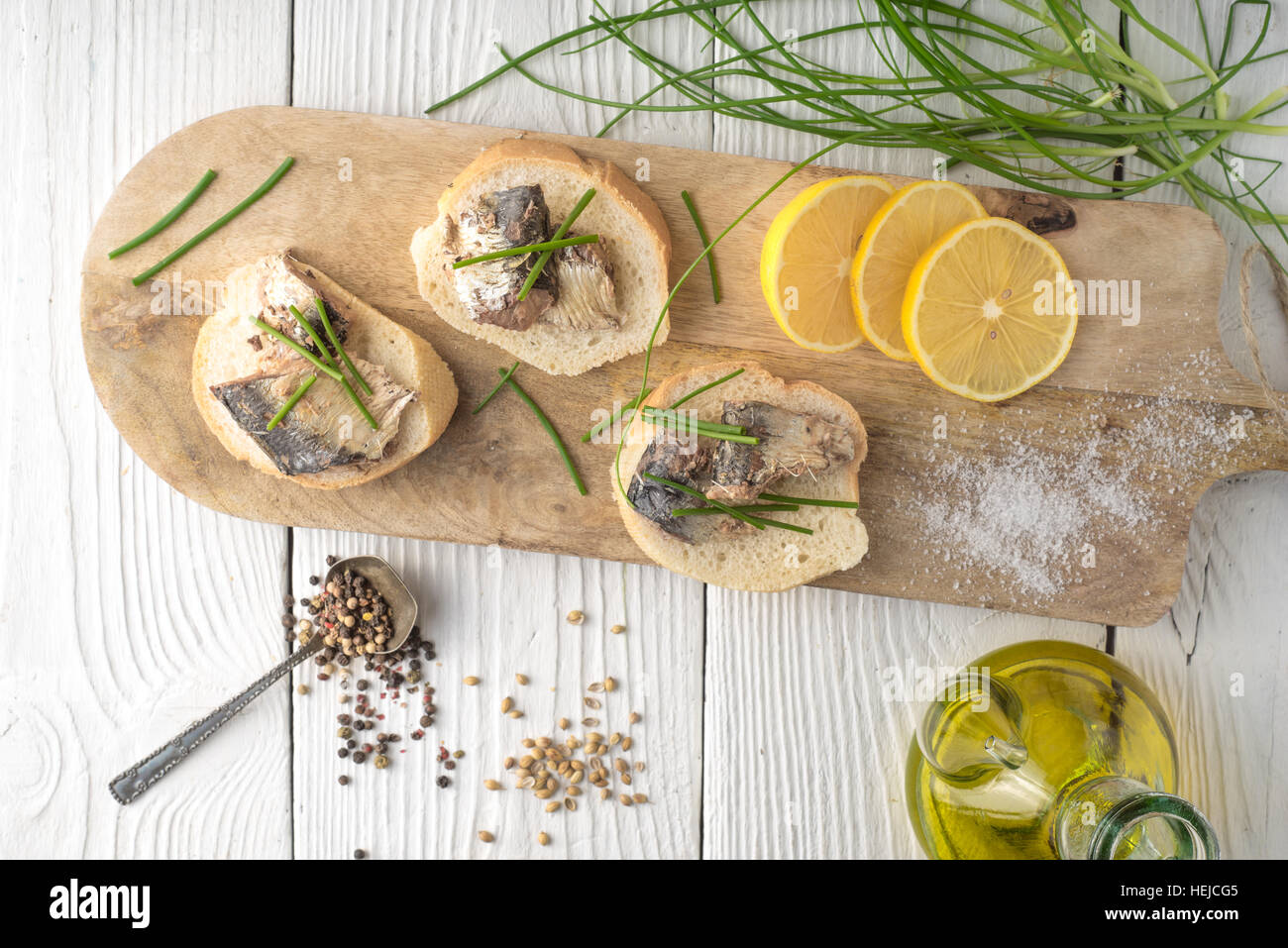 Sandwiches with sardines and onions on a cutting board horizontal - Stock Image