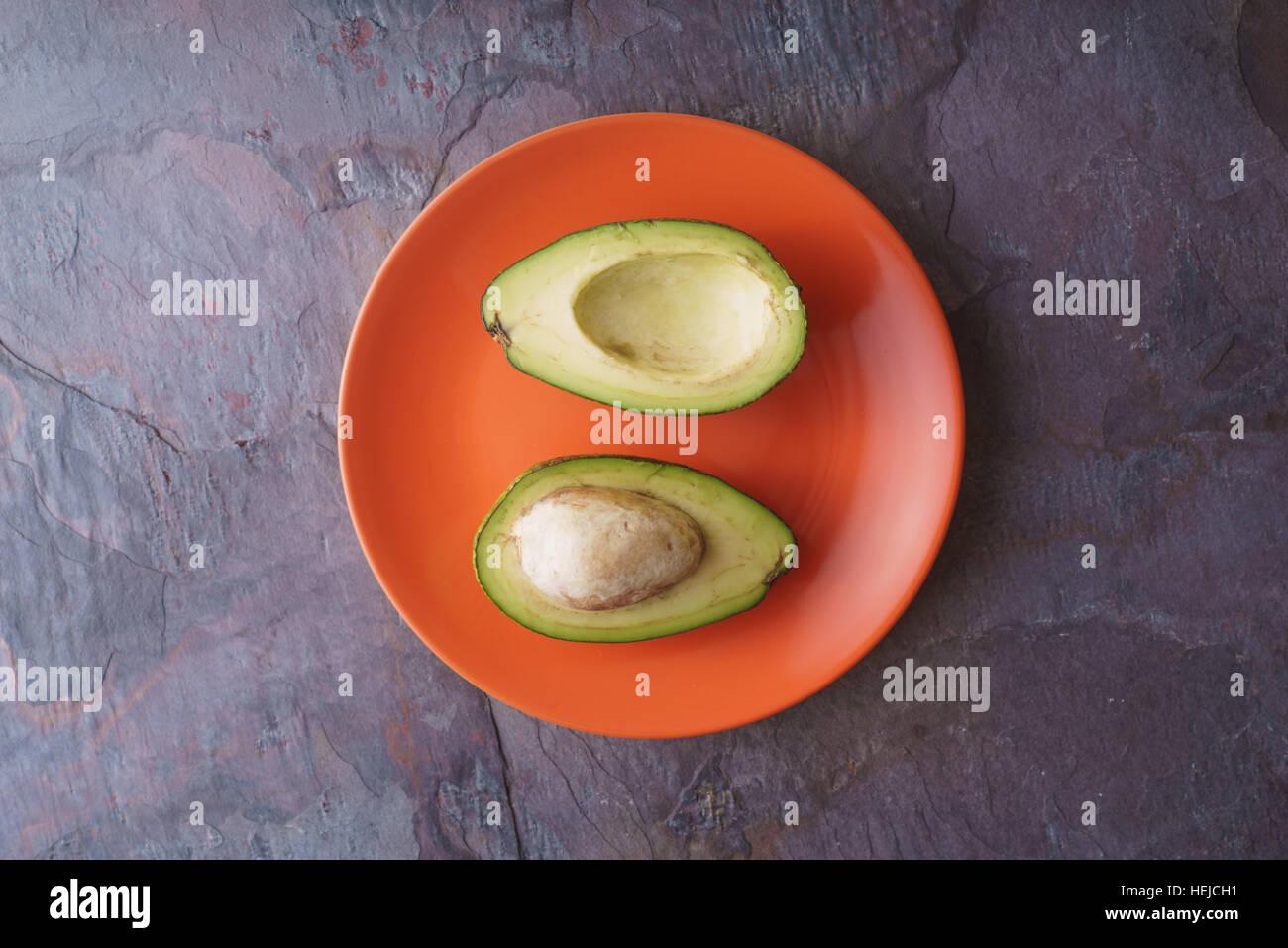 Avocado halves lie on an orange plate on a slate horizontal - Stock Image
