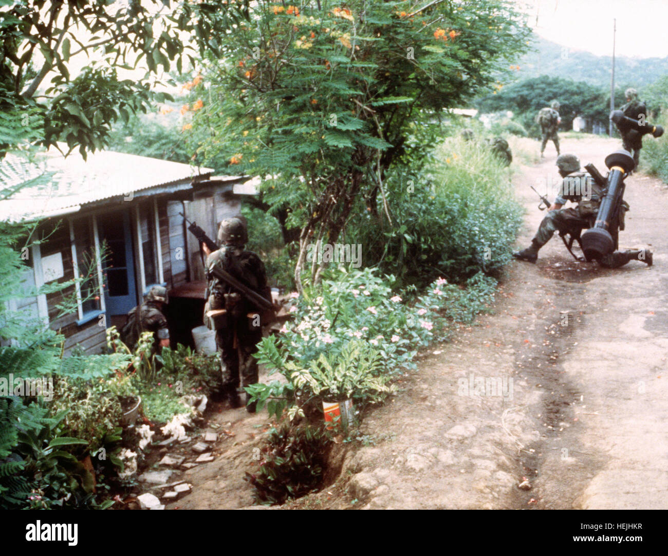 Members of the 82nd Airborne Division approach a building while on patrol during Operation URGENT FURY.  Two of - Stock Image