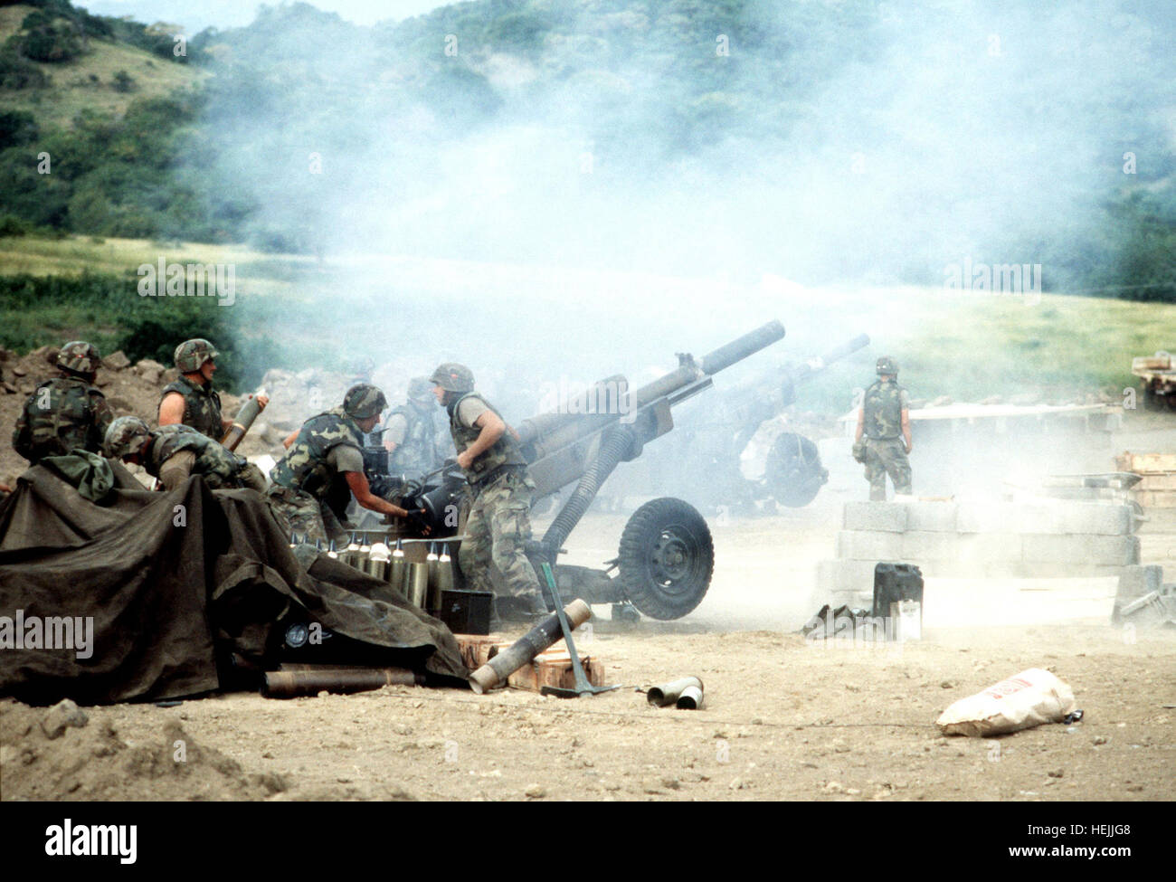 82nd Airborne artillery personnel load and fire M102 105 mm howitzers during Operation URGENT FURY. M102 howitzers - Stock Image