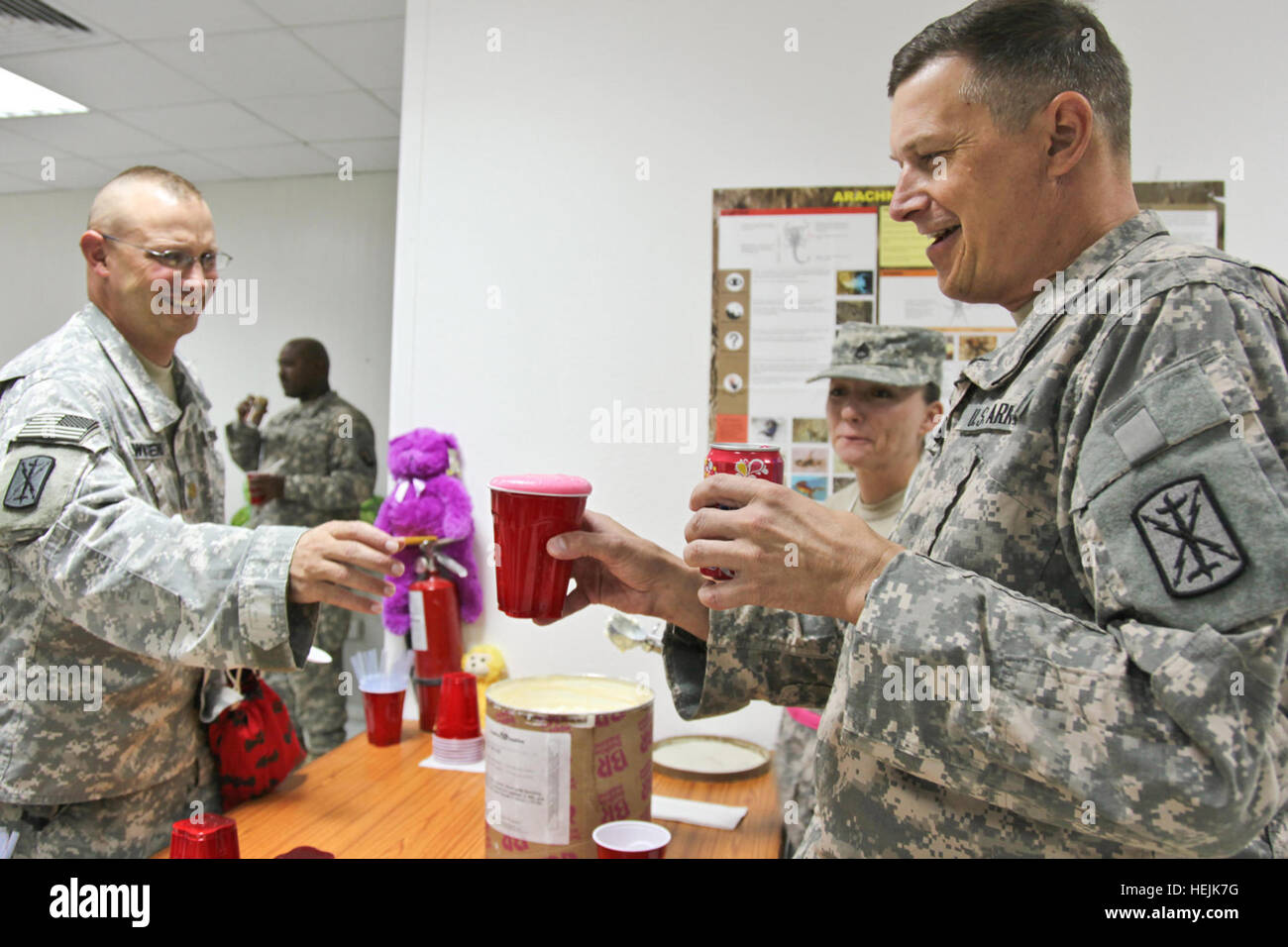 Maj. Michael King, chaplain, pushes the envelope of his strawberry soda float making skills while Maj. blank Townsend - Stock Image