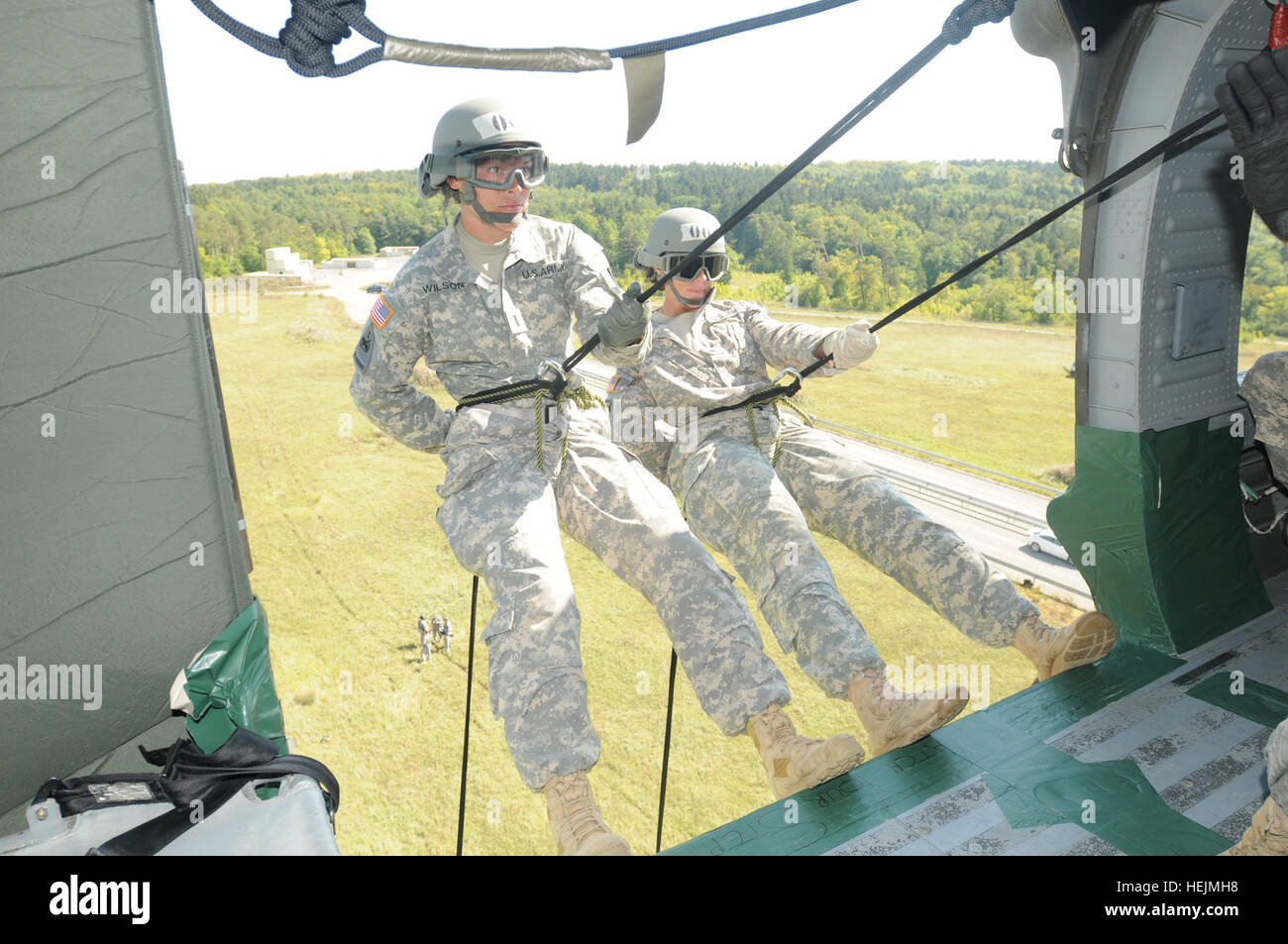 Two air assault students stand on the edge of a UH60 Black Hawk and prepare to rappel to the ground as the helicopter - Stock Image