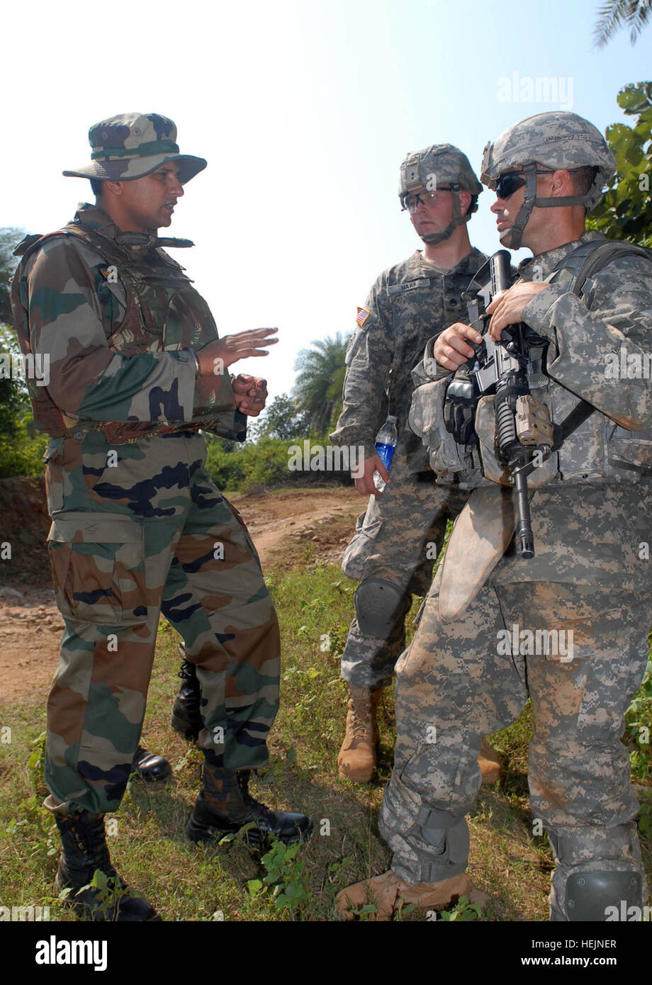 """CAMP BUNDELA, India (Oct. 15, 2009) – An Indian Army officer from the 7th mechanized Infantry Regiment, prepares U.S. Army Sgt.1st Class Michael Moyer, Troop C, 2nd Squadron, 14th Cavalry Regiment """"Strykehorse,"""" 2nd Stryker Brigade Combat Team, 25th Infantry Division, from Schofield Barracks, Hawaii, for the jungle range during range training at Exercise Yudh Abhyas 09, Oct. 15. YA09 is a bilateral exercise involving the Armies of India and the United States. US Army 53412 Range Training in India fires up Strykehorse Soldiers Stock Photo"""