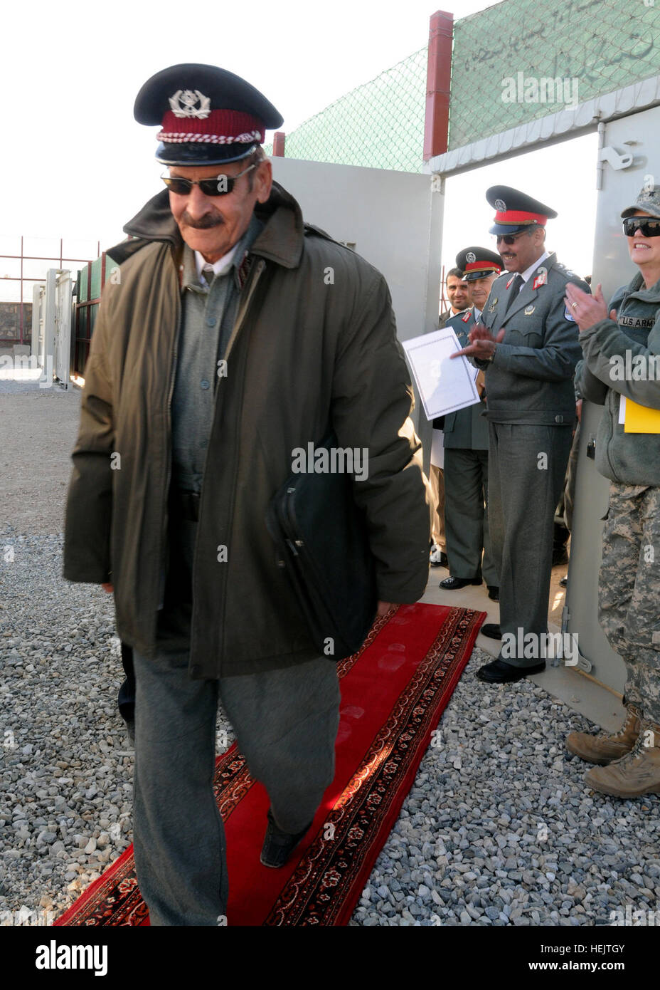 Retired Afghan National Police officer Gul Muhammad Kakar is applauded as the first to officially enter Afghanistan's - Stock Image