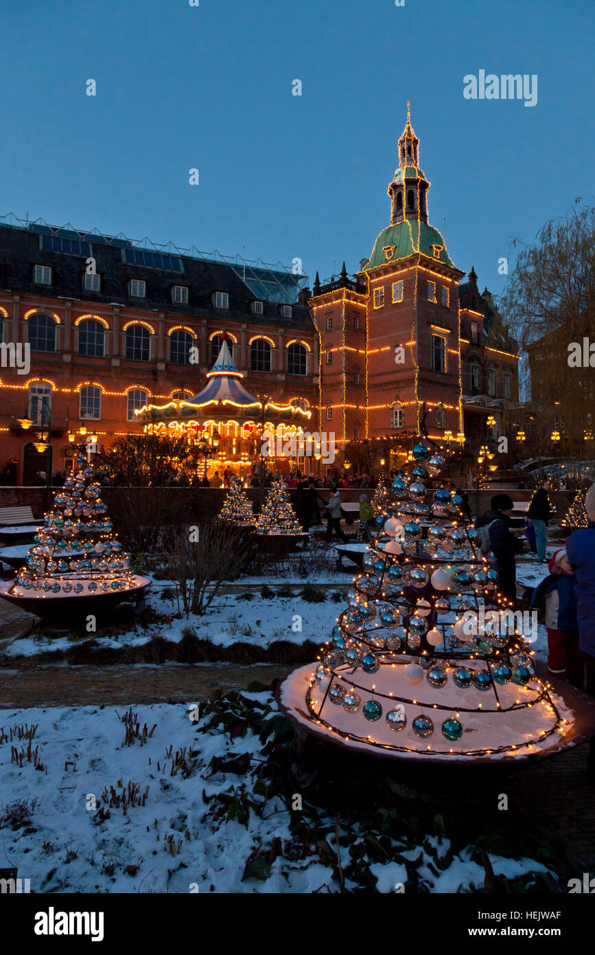 Illuminated H.C. Andersen Castle in the Tivoli Gardens with Christmas decorations, a merry-go round, and real snow - Stock Image
