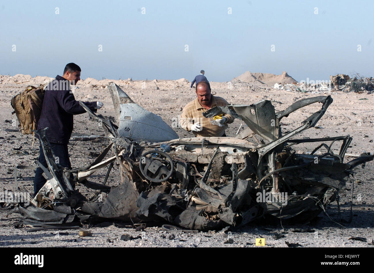 Iraqi law enforcers search for clues among and beyond an exploded car during a training session sponsored by the - Stock Image