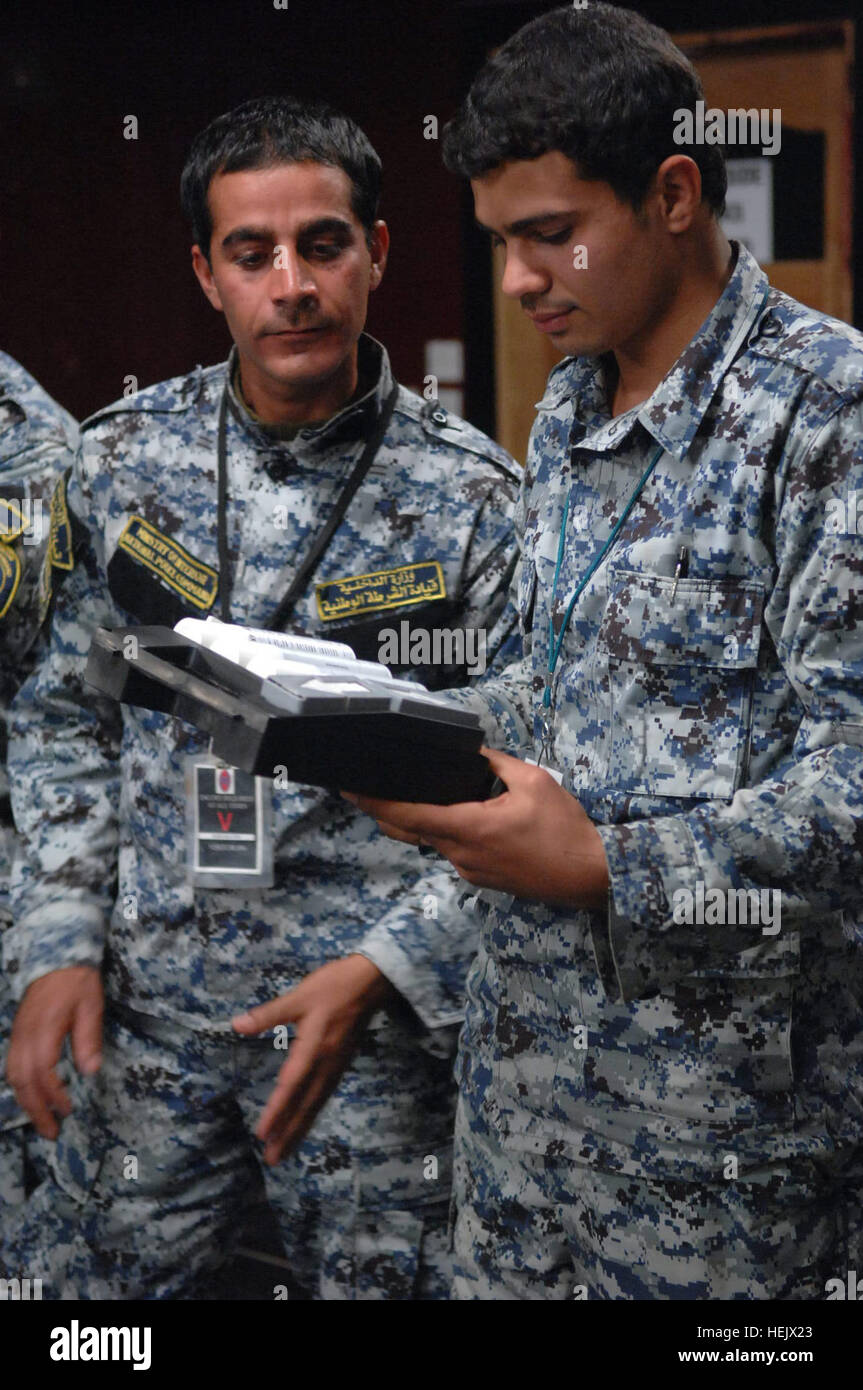Iraqi federal police officers inspect training supplies handed to them during joint training on Forward Operating - Stock Image