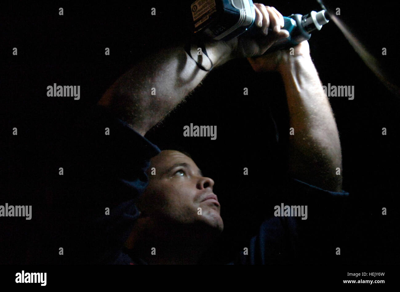 Navy Petty Officer 3rd Class Robert Hicks, an aviation structural mechanic, performs maintenance on a timer check Stock Photo