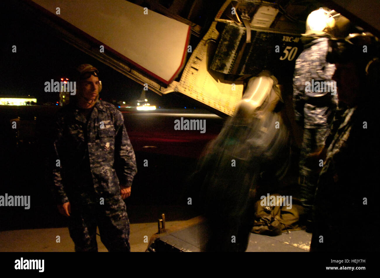 Airmen from Fleet Logistics Support Squadron 40 board passengers on a C-2 Greyhound aircraft at U.S. Naval Station Stock Photo