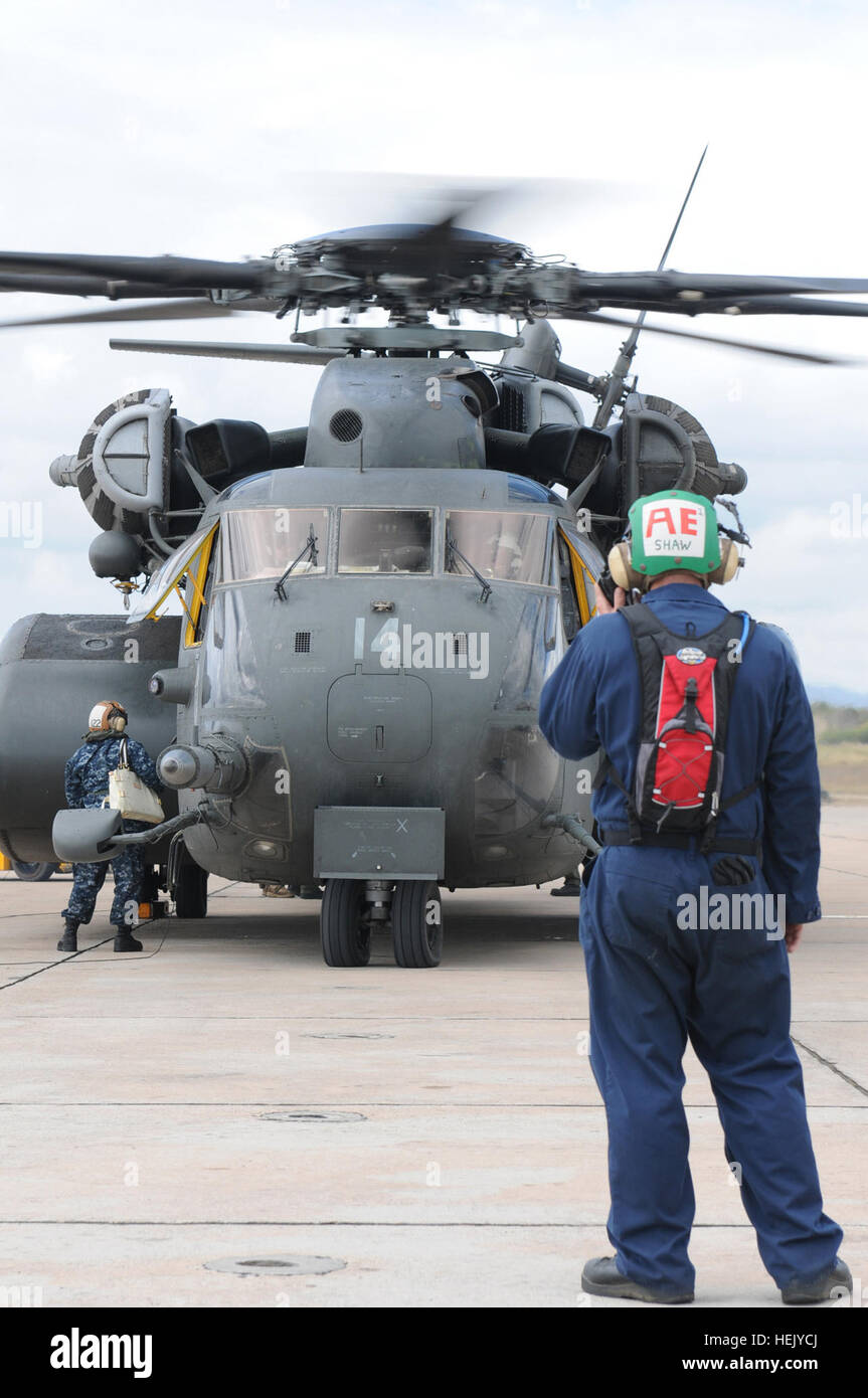 A crewman with Helicopter Mine Countermeasures Squadron 14 prepares an MH-53E Sea Dragon for a flight transporting Stock Photo