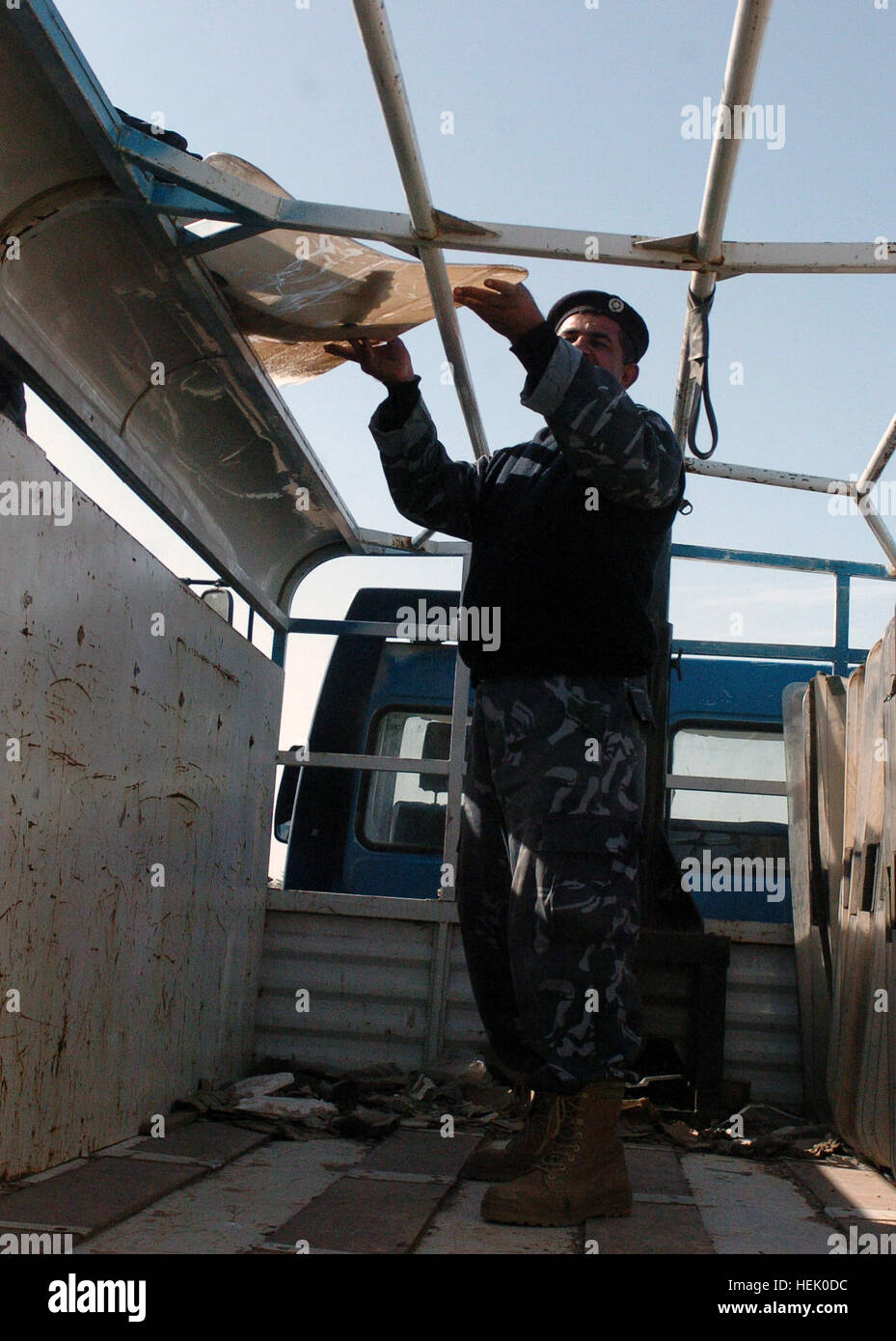 An Iraqi police officer stands on an empty truck that was later filled with civil disturbance equipment, such as - Stock Image