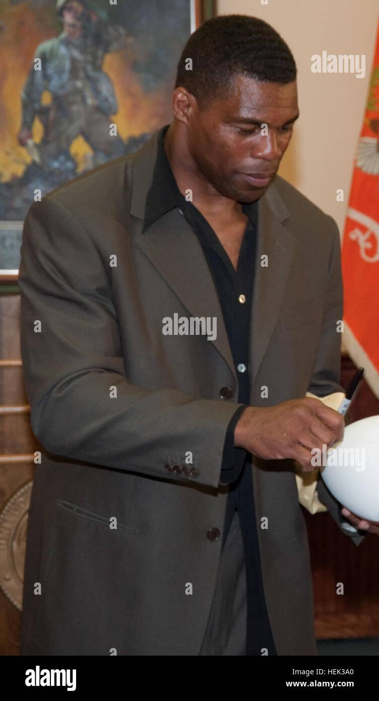 Heisman Trophy Winner Herschel Walker, left, signs a football for