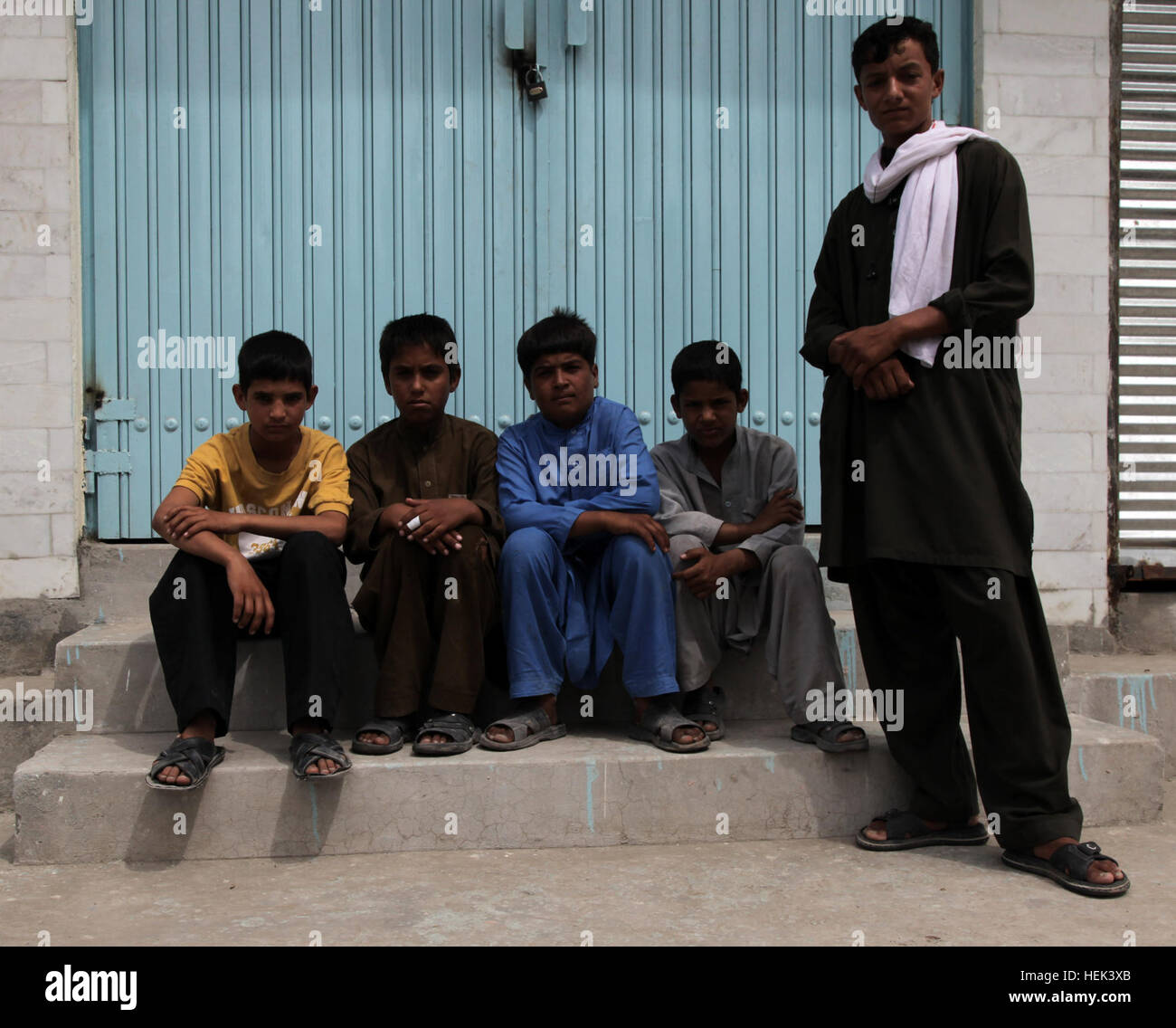 Local Afghanistan boys hang out in front of an abandoned building in downtown Jalalabad, Afghanistan, June 7. PRT - Stock Image